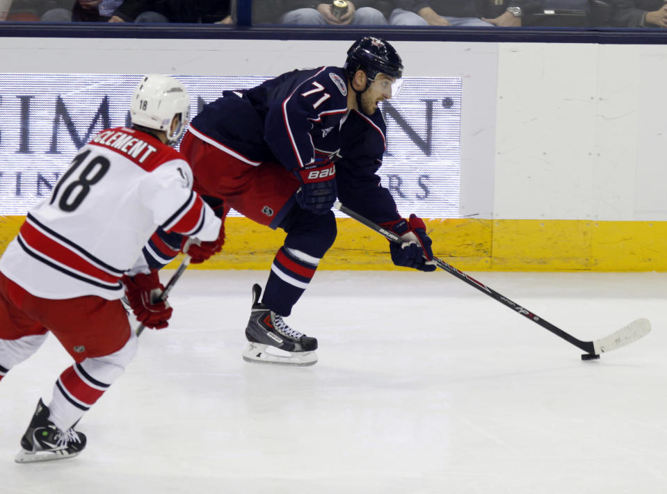 Columbus Blue Jackets' Nick Foligno, right, carries the puck against Carolina Hurricanes' Jay McClement during the third period of an NHL hockey game in Columbus, Ohio, Tuesday, Nov. 4, 2014. (AP Photo/Paul Vernon)