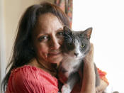 In this Wednesday, June 30, 2021, photo Veronica Perez hugs her cat, Brooklyn, at her new home at a Homekey site in Los Angeles. She took residence in one of 6,000 new units built statewide over the last year as part of Project Homekey. The California program started in June 2020 is re-purposing vacant hotels, motels and other unused properties as permanent supportive housing for the homeless. (AP Photo/Damian Dovarganes)