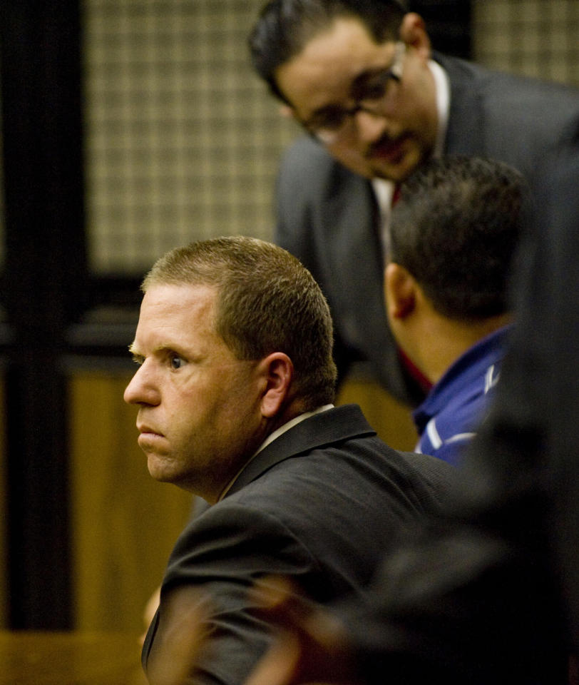 Fullerton police officer Jay Cicinelli sits among attorneys as he waits for his arraignment hearing to begin in Orange County Superior Court on Wednesday, Sept. 21, 2011 in Santa Ana, Calif. Prosecutors charged one police officer with murder and another with manslaughter in the killing of 37-year-old Kelly Thomas, an unarmed, mentally ill homeless man who was pummeled, shocked with a Taser and slammed with the butt of a stun gun in a beating that lasted nearly 10 minutes. Manuel Ramos was charged with one count each of second-degree murder and involuntary manslaughter . Cicinelli was charged with one count each of involuntary manslaughter and excessive force. (AP Photo/Paul Rodriguez)