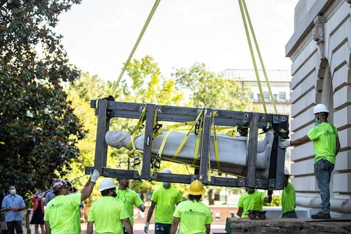 Workers use a crane to remove the Jefferson Davis statue from the Kentucky state Capitol in Frankfort, Ky., on Saturday, June 13, 2020.