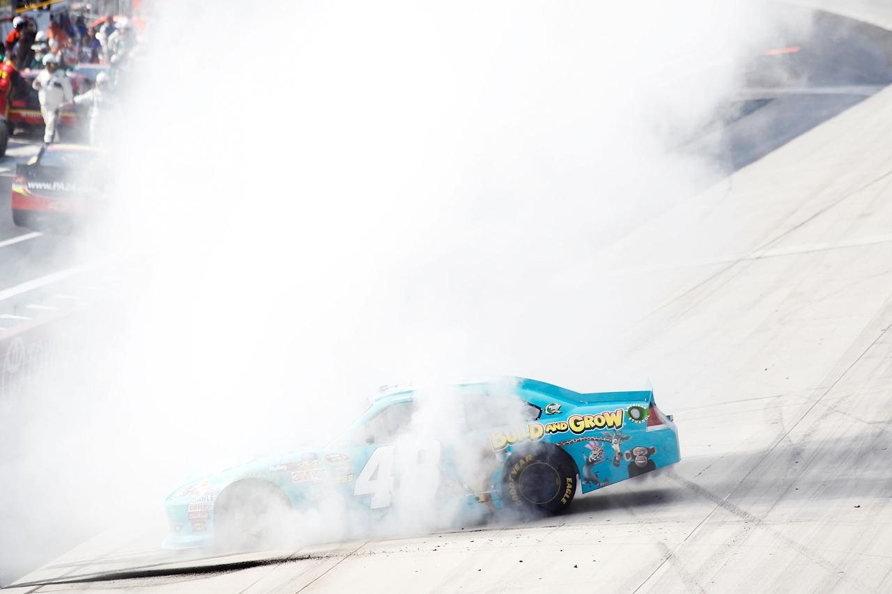 DOVER, DE - JUNE 03:  Jimmie Johnson, driver of the #48 Lowe's Madagascar Chevrolet, performs a burnout to celebrate winning the NASCAR Sprint Cup Series FedEx 400 benefiting Autism Speaks at Dover International Speedway on June 3, 2012 in Dover, Delaware.  (Photo by Todd Warshaw/Getty Images)