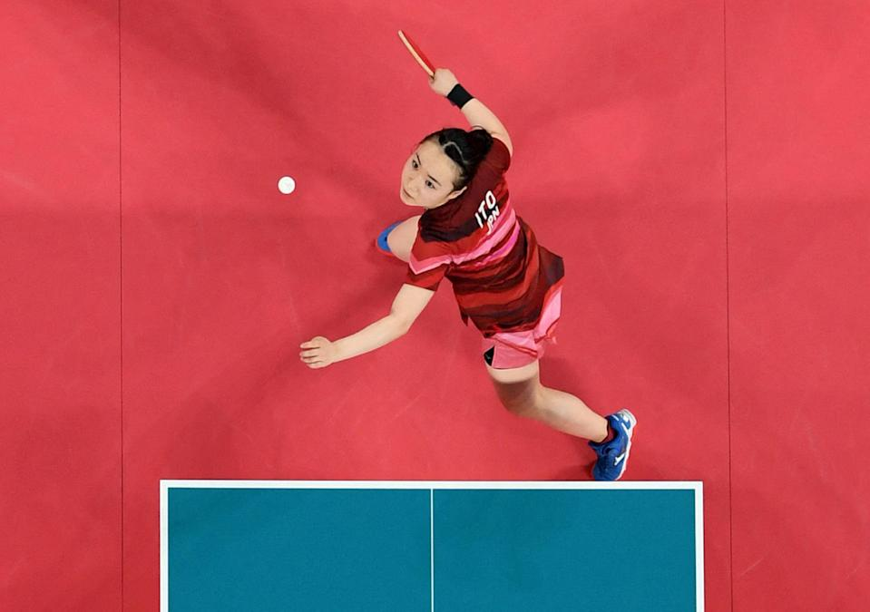 <p>Japan's Mima Ito hits a shot against China's Xu Xin and Liu Shiwen (not pictured) in their July 26 mixed doubles table tennis final match.</p>