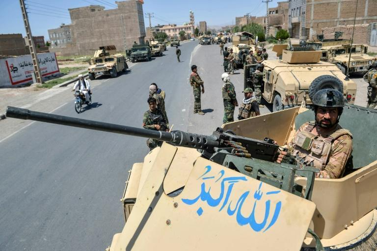 An Afghan National Army commando stands guard on top of a vehicle in Herat province amid skirmishes with the Taliban