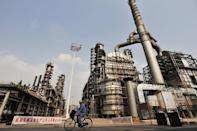 A worker rides through a Sinopec refinery in Wuhan, central China's Hubei province, May 10, 2011. China is already the biggest energy user in the world and the second-largest oil consumer after the United States