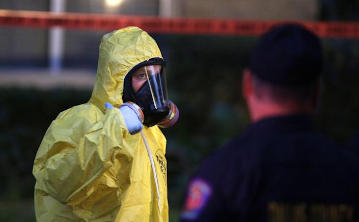 A hazardous materials worker looks up while finishing cleaning outside nurse Nina Pham's Dallas apartment. (AP Photo/LM Otero)