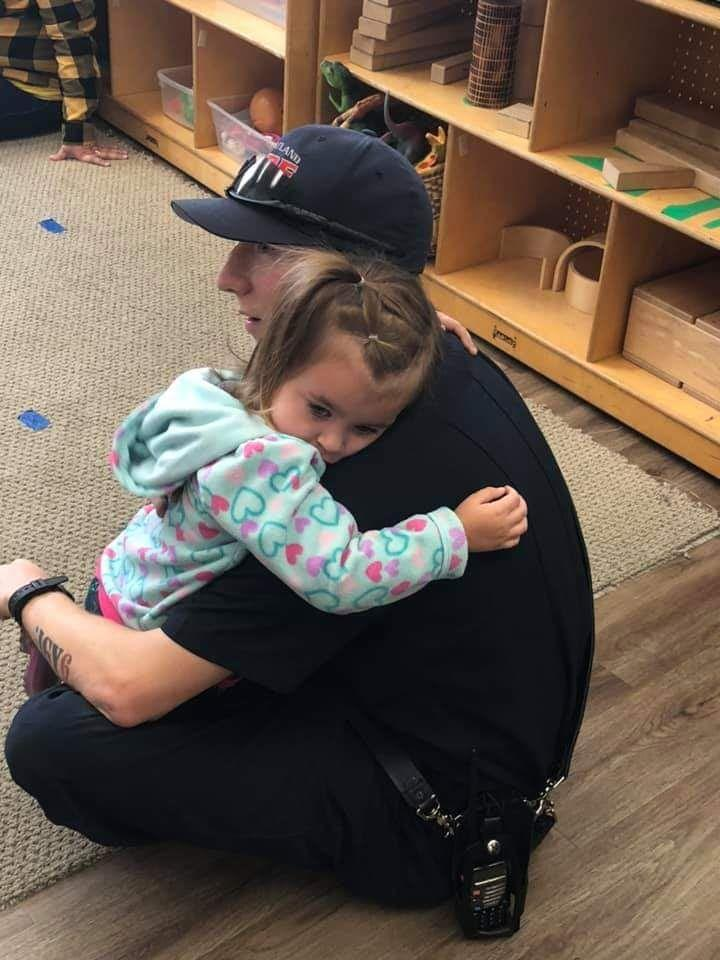 Wheatland Fire Authority officer Anthony Banas with Kayli, an autistic girl he comforted with a hug during a school visit.