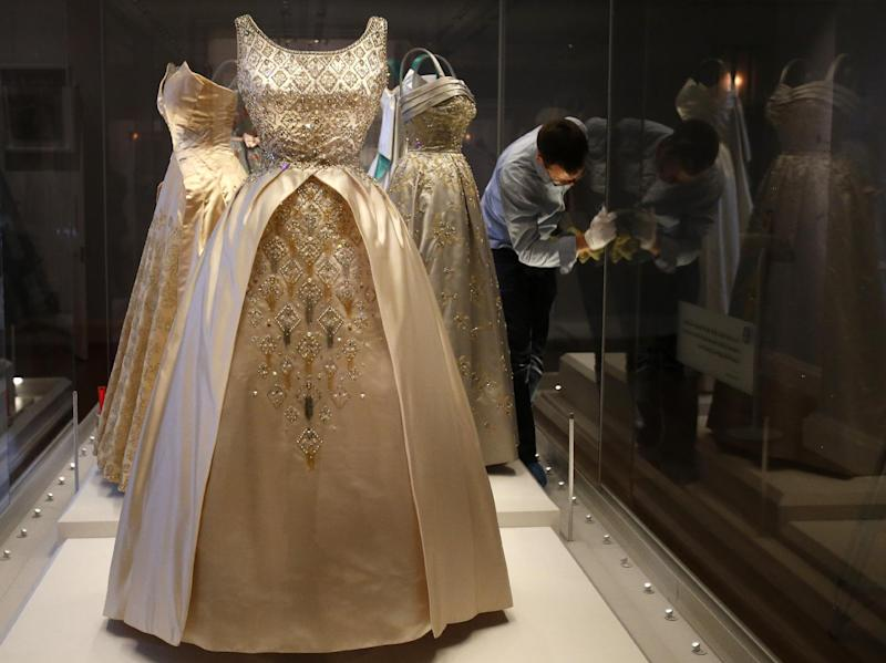 In this photo taken Monday, July 1, 2013, an employee cleans the glass cabinet displaying dresses worn by Queen Elizabeth II at the Fashion Rules exhibition at Kensington Palace in London. Opening on 4 July, a new glamorous exhibit at Kensington Palace showcases how the styles of three royal ladies; Queen Elizabeth II, her sometimes risque sister Margaret, and the glamorous Princess Diana, each reflected and influenced the trends of their fashion heyday. (AP Photo/Frank Augstein)