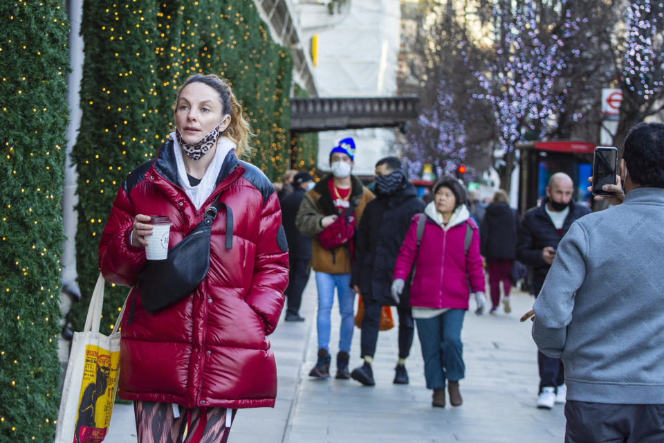 Shoppers walk past Christmas decorations in New Bond Street, London. Photo: Pietro Recchia/SOPA/LightRocket via Getty