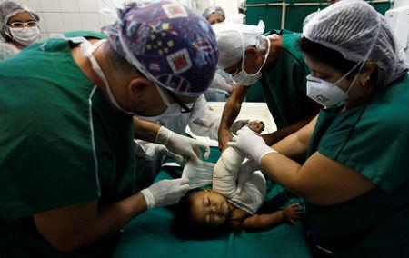 Doctors wrap a child's burnt skin with sterilised tilapia fish skin at Dr. Jose Frota Institute in the northeastern costal city of Fortaleza, Brazil, May 3, 2017. REUTERS/Paulo Whitaker
