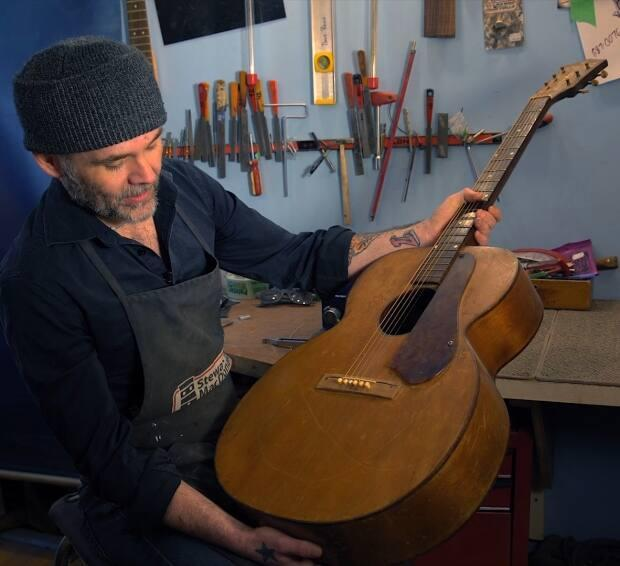 O'Brien's guitar technician Chris Kearsey assesses the repairs needed on a 1950s-era S.S. Stewart guitar. (Mike Simms/CBC - image credit)