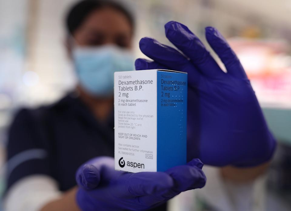 A member of staff at a pharmacy in London holds a packet of anti-inflammatory drug dexamethasone, which has been hailed as a ground-breaking treatment for hospital patients seriously ill with COVID-19. (Photo: Yui Mok - PA Images via Getty Images)