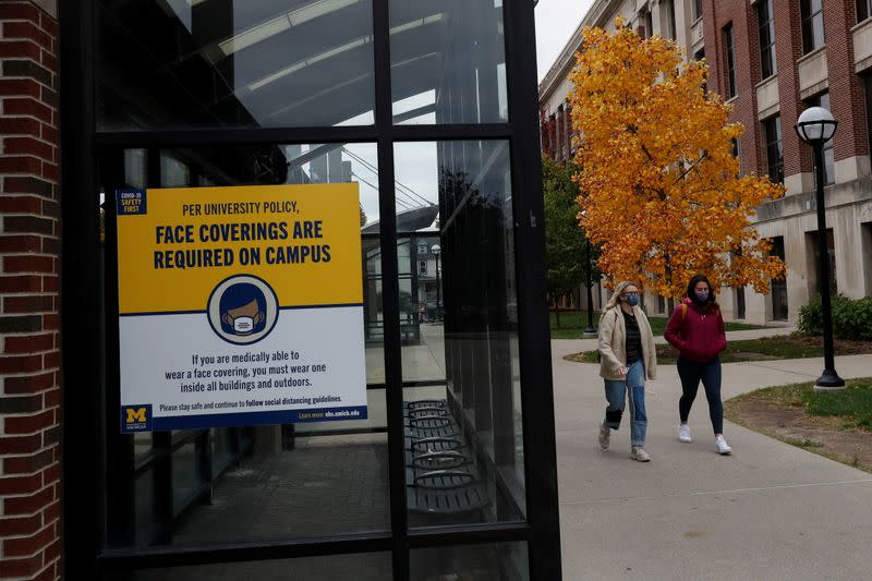 Women with protective face masks walk on the University of Michigan campus in Ann Arbor