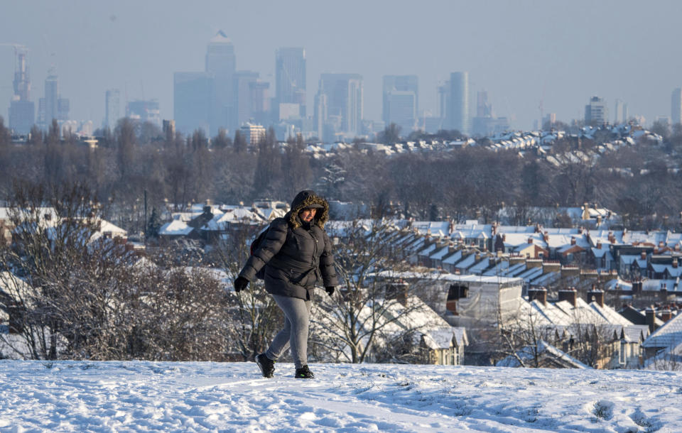 <p>A woman walks over Blythe Hill in south London. Britain, which is buffered by the Atlantic Ocean and tends to have temperate winters, saw heavy snow in some areas that disrupted road, rail and air travel and forced hundreds of schools to close. (Dominic Lipinski/PA via AP) </p>