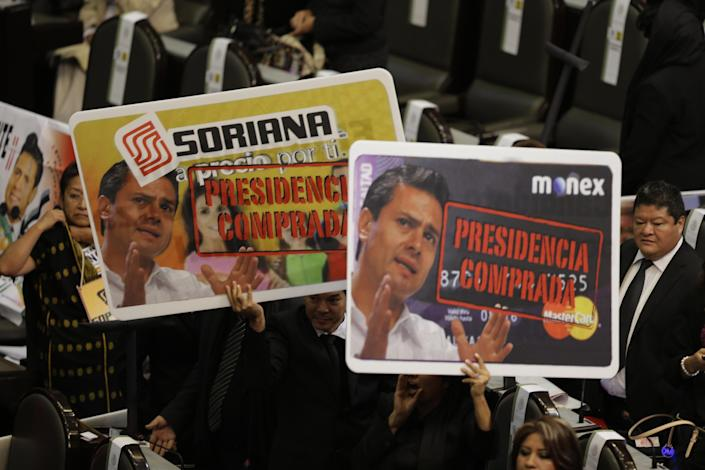"""Opposition lawmakers hold up banners showing photos of Mexico's president-elect Enrique Pena Nieto, saying """"Purchased Presidency"""" during the presidential swearing in ceremony at the National Congress in Mexico City, Saturday Dec. 1, 2012. Pena Nieto became Mexico's new president on Saturday, bringing the old ruling party back to power after a 12-year hiatus amid protests inside and outside the congressional chamber where he swore to protect the constitution and laws of the land. (AP Photo/Dario Lopez-Mills)"""