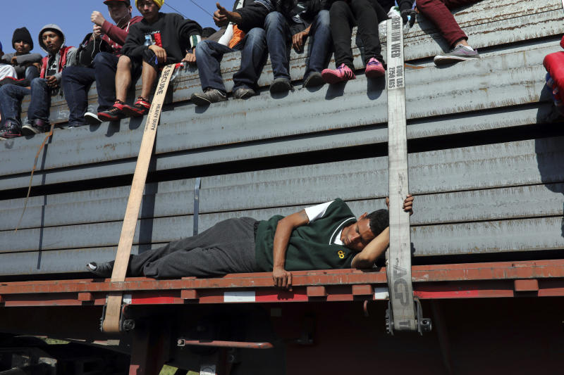 A Central American migrant, part of the caravan hoping to reach the U.S. border, sleeps while getting a ride on a truck with others, in Celaya, Mexico, Sunday, Nov. 11, 2018. Local Mexican officials were once again Sunday helping thousands of Central American migrants find rides on the next leg of their journey toward the U.S. border. (AP Photo/Rodrigo Abd)