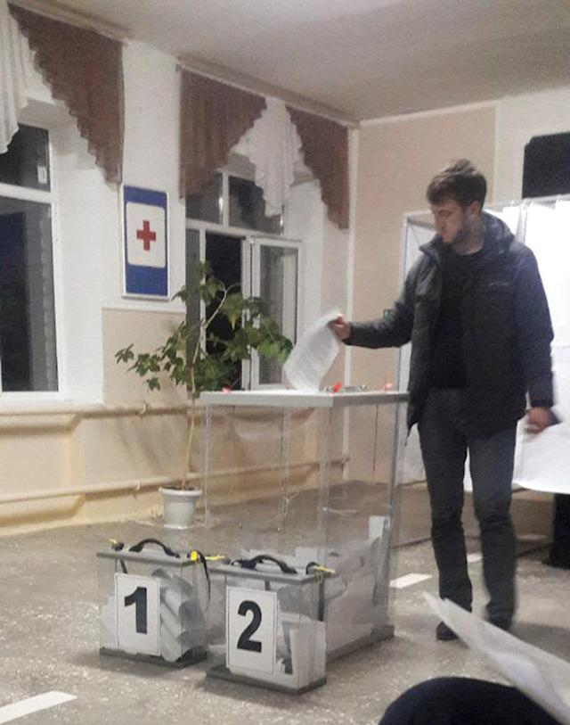 """A voter casts a ballot at a polling station number 215 during the presidential election in Ust-Djeguta, Russia March 18, 2018. The voter was asked by a Reuters reporter why he was voting for a second time and answered """"No, this is the first time I voted"""". Picture taken March 18, 2018. REUTERS/Polina Nikolskaya"""