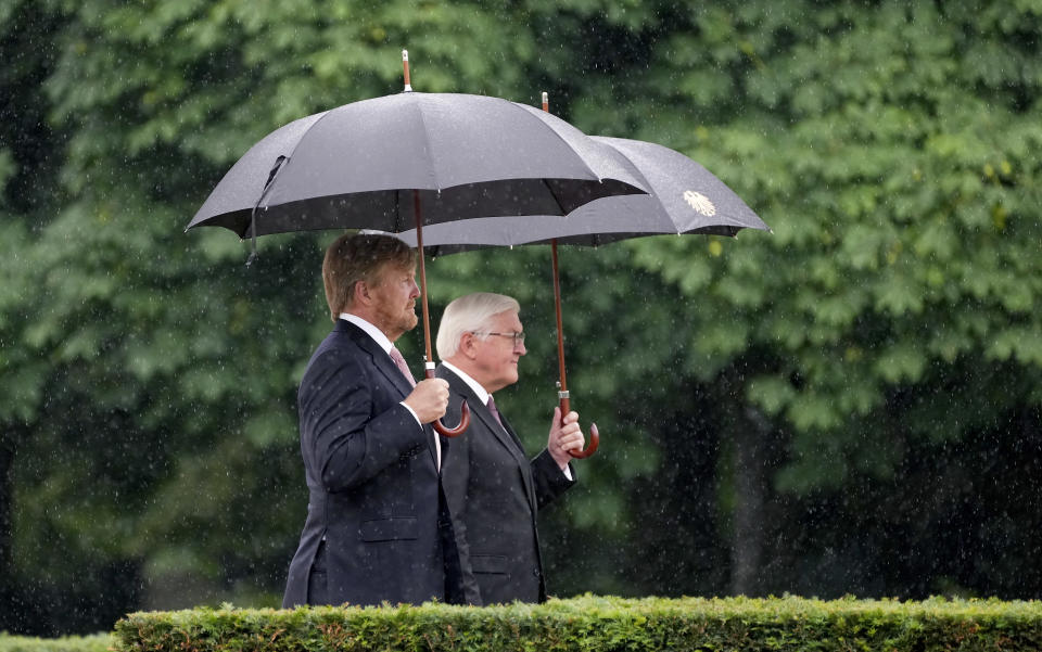 German President Frank-Walter Steinmeier, right, and Dutch King Willem-Alexander, left, attend a military welcome ceremony as part of a meeting in Berlin, Germany, Monday, July 5, 2021. The Royals arrived in Germany for a three-day visit that was delayed from last year because of the coronavirus pandemic. (AP Photo/Michael Sohn)