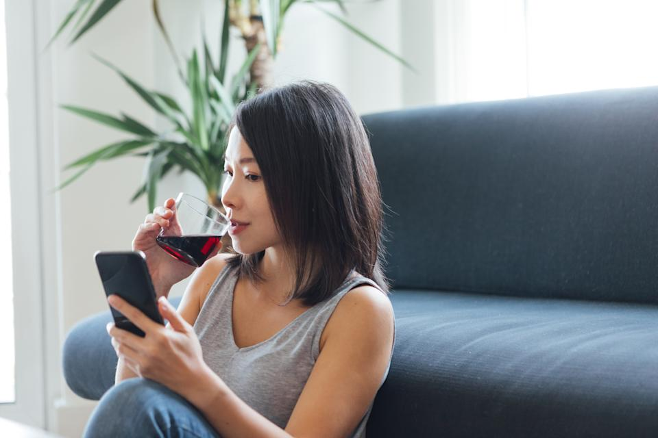 Head shot of young beautiful woman drinking wine while using smartphone at home during the day.