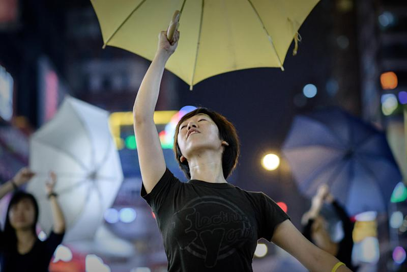 Pro-democracy protesters dance with umbrellas, a month after they first took to the streets, in the Mongkok district of Hong Kong on October 28, 2014 (AFP Photo/Philippe Lopez)