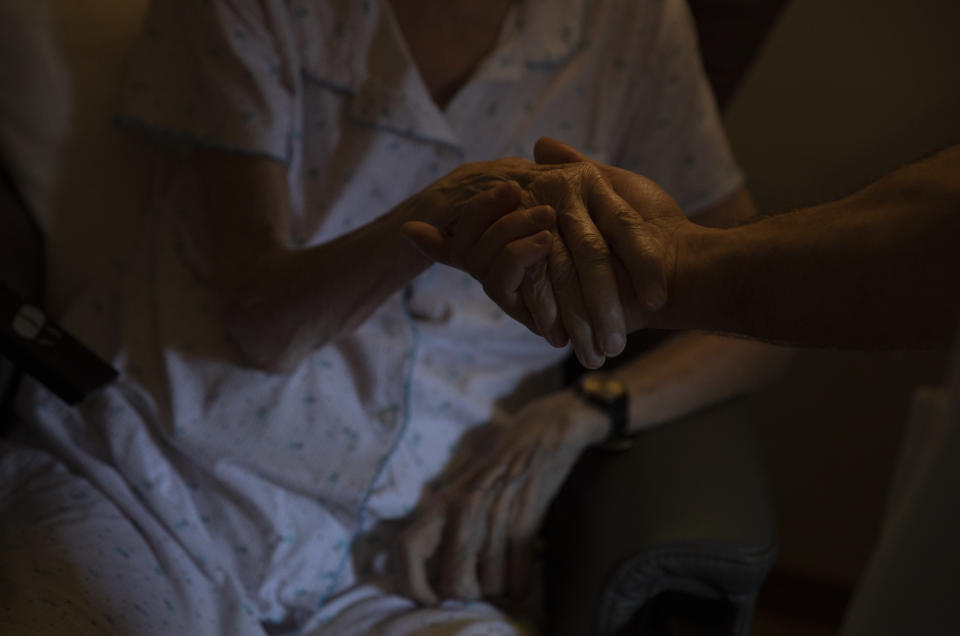 A healthcare worker holds the hand of a resident at the CHC nursing home in Landenne, Belgium, Wednesday, Nov. 4, 2020. Belgium, proportionally still the worst-hit nation in Europe when it comes to coronavirus cases, said Wednesday that there were increasing signs of that a turning point in the crisis was drawing close. The Belgian Army has been deployed to help several hard hit areas in the country including nursing homes. (AP Photo/Virginia Mayo)
