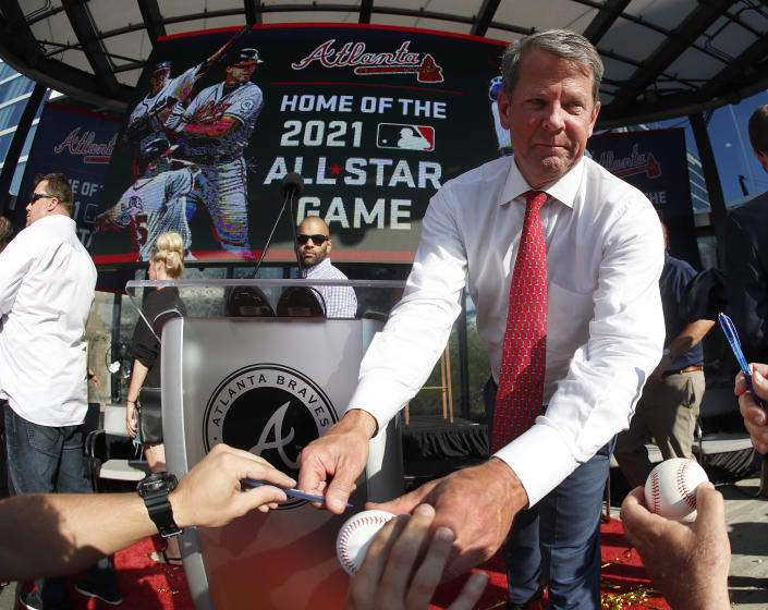 Georgia Gov. Brian Kemp signs a baseball after a ceremony to announce that Atlanta will host baseball's 2021 All-Star Game, Wednesday, May 29, 2019, in Atlanta. (AP Photo/John Bazemore)