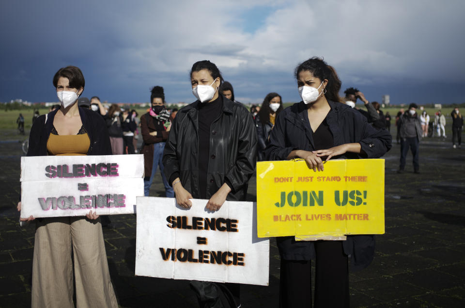 Women hold posters as they attend a rally marking the one-year anniversary of the killing of George Floyd, at the former airport Tempelhof in Berlin, Germany, Tuesday. (AP Photo/Markus Schreiber)
