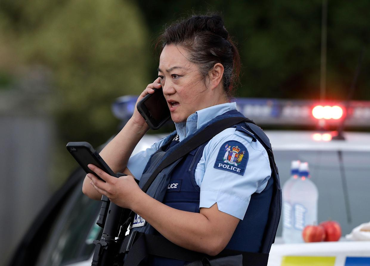 A police officer talks on her phone as a roadblock near a mass shooting at a mosque in Linwood, Christchurch, New Zealand, Friday, March 15, 2019. (Photo: Mark Baker/AP)