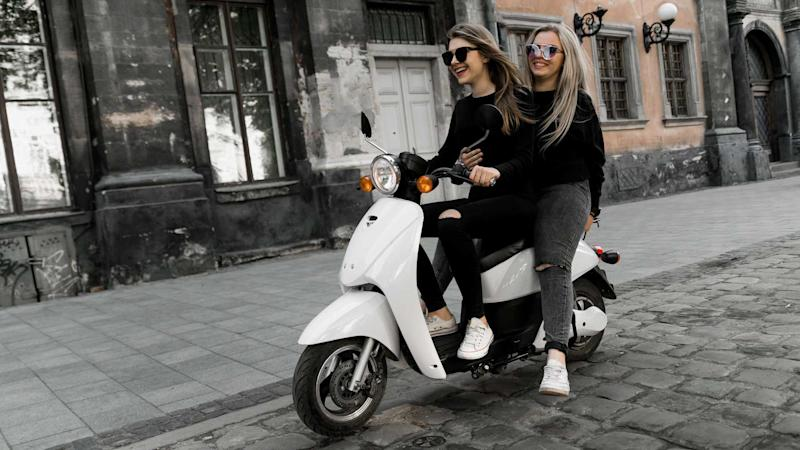 Young women riding vintage scooter