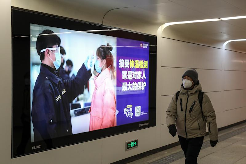 A person wears a protective face mask in Beijing while walking past a sign warning people to wear face masks due to coronavirus.