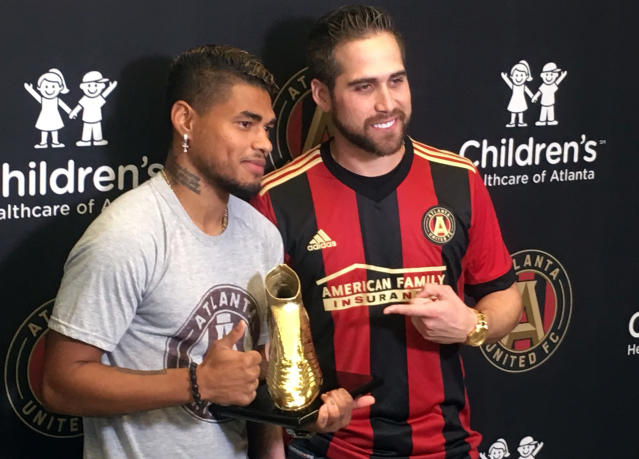 Atlanta Braves outfielder Ender Inciarte, right, poses with Atlanta United's Josef Martinez, after presentg Martinez with the MLS Golden Boot award during a news conference, Thursday, Nov. 1, 2018, in Marietta, Ga. The Atlanta United striker scored 31 goals this season, easily eclipsing the league record. Both athletes are from Venezuela. (AP Photo/Paul Newberry)