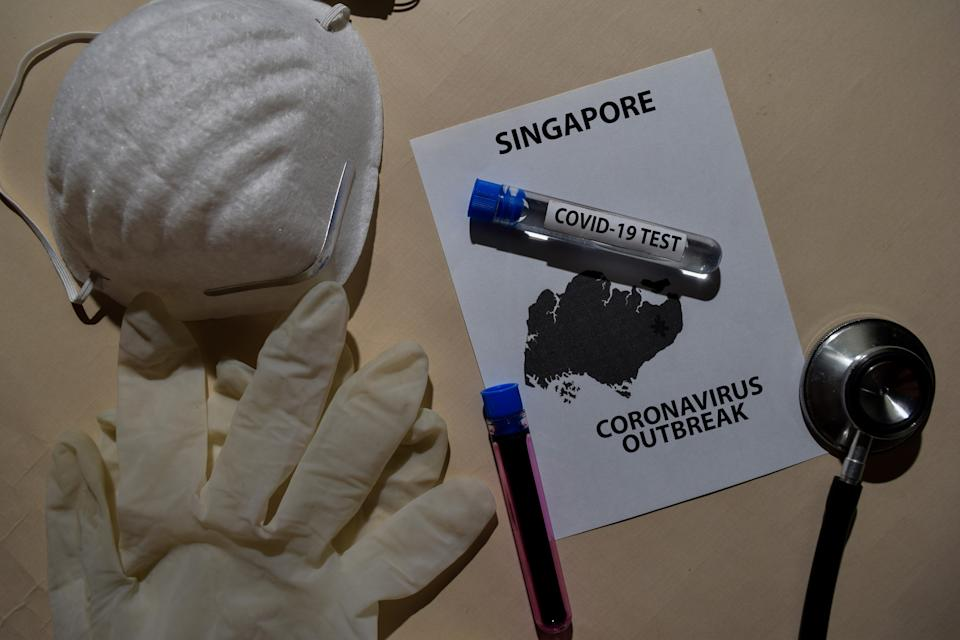 Corona Virus outbreak with Singapore map printed on paperwork. Vaccine Covid-19 Test isolated on office desk. Awareness Prevention. Medical concept