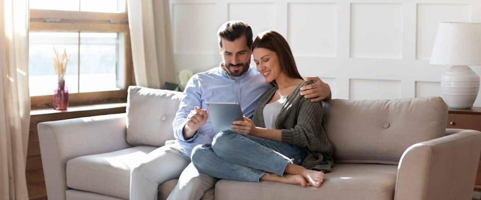 Happy looking couple sitting closely on couch, looking at tablet together