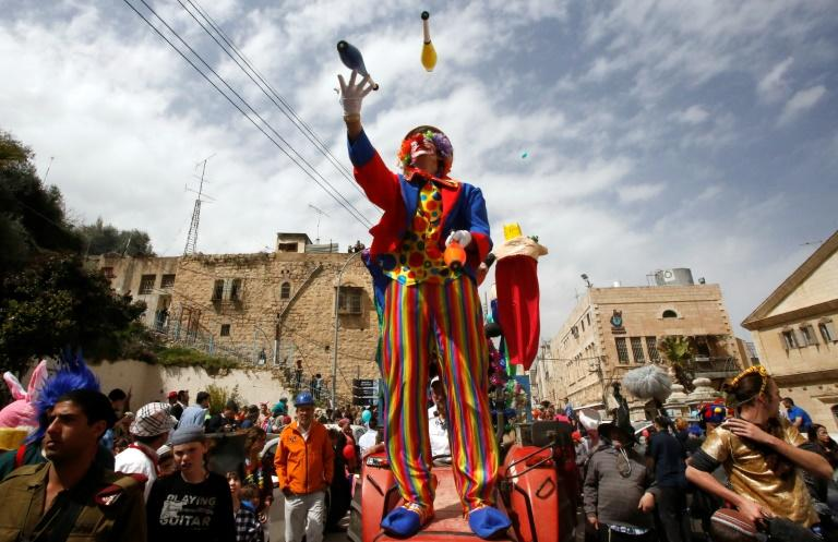Israeli settlers join a parade marking the Jewish holiday of Purim in the occupied West Bank town of Hebron, on March 12, 2017