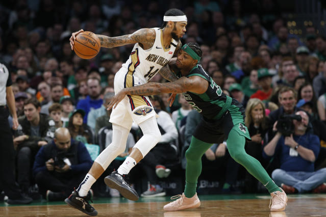 Boston Celtics' Marcus Smart tries to reach in for the ball held by New Orleans Pelicans' Brandon Ingram during the first quarter of an NBA basketball game Saturday, Jan. 11, 2020, in Boston. (AP Photo/Winslow Townson)