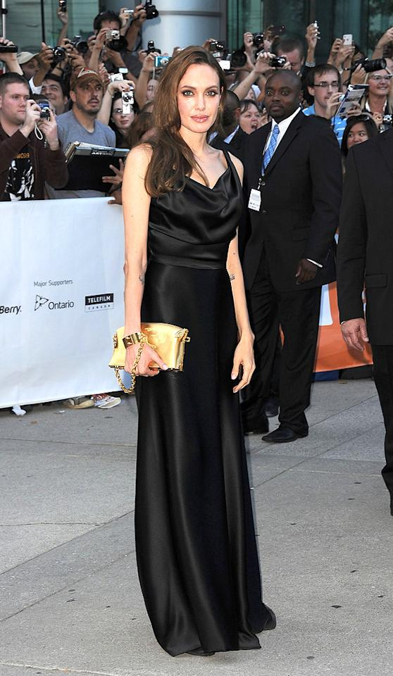 """Also spotted in Toronto ... Oscar winner Angelina Jolie, who attended the premiere of partner Brad Pitt's new movie, """"Moneyball,"""" in a dramatic, black satin Vivienne Westwood gown and gold Louis Vuitton clutch, which was attached to a matching cuff wrapped around her wrist. Jason Merritt/<a href=""""http://www.gettyimages.com/"""" target=""""new"""">GettyImages.com</a> - September 9, 2011"""