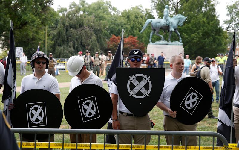 White supremacists, holding shields with a symbol of Vanguard America on them, gather under a statue of Robert E. Lee during a rally in Charlottesville, Virginia, U.S., August 12, 2017.