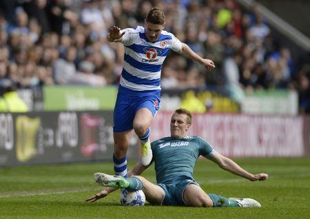 Reading's George Evans in action with Wigan Athletic's Dan Burn
