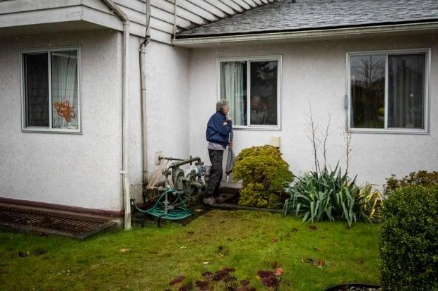 A man visits his 94-year-old mother, who tested positive for COVID-19 at the Tabor Home assisted living centre in Abbotsford, B.C., in November, 2020.