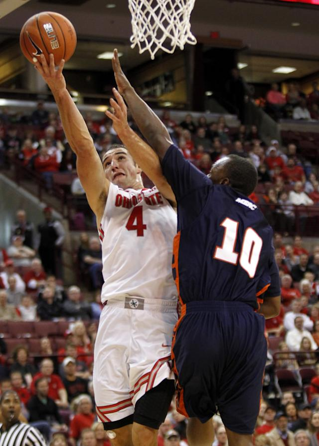 Ohio State's Aaron Craft , left, goes up for a shot against Morgan State's Emmanuel Matey during the first half of an NCAA college basketball game in Columbus, Ohio, Saturday, Nov. 9, 2013. (AP Photo/Paul Vernon)