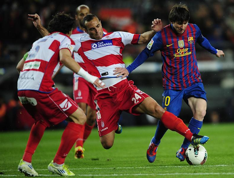 FC Barcelona's Lionel Messi, from Argentina, right, duels for the ball against Granada's Moises Hurtado during a Spanish La Liga soccer match at the Camp Nou stadium in Barcelona, Spain, Tuesday, March 20, 2012. (AP Photo/Manu Fernandez)