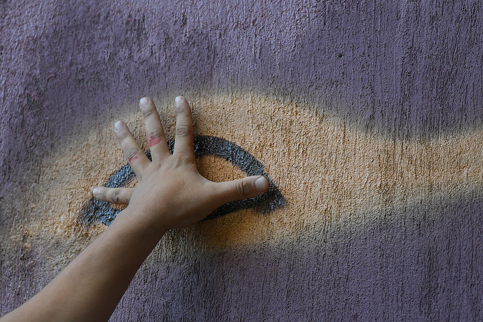 Street artist Wolfgang Salazar uses his hand to measure proportions as he begins to paint the eyes of his most recent mural, in the Boleita neighborhood of Caracas, Venezuela, Monday, Dec. 28, 2020. Salazar says he's part of a campaign to legitimize the street art of graffiti and has been invited to several countries in Latin America and Europe to paint murals. (AP Photo/Matias Delacroix)