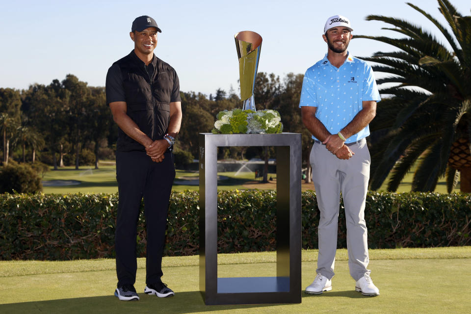 Max Homa, right, poses with his trophy next to Tiger Woods on the practice green after winning the Genesis Invitational golf tournament at Riviera Country Club, Sunday, Feb. 21, 2021, in the Pacific Palisades area of Los Angeles. (AP Photo/Ryan Kang)