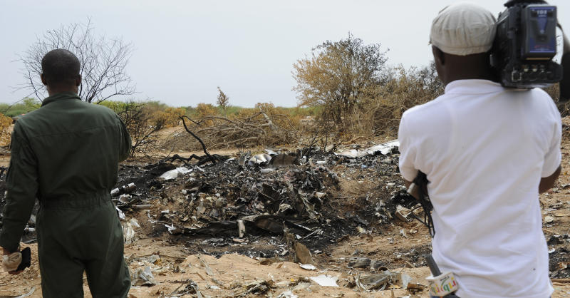 A Burkina Faso Air Force soldier and a journalist look at debris from Air Algerie Flight AH 5017 scattered at the crash site in Mali's Gossi region, west of Gao, on July 26, 2014 (AFP Photo/Sia Kambou)