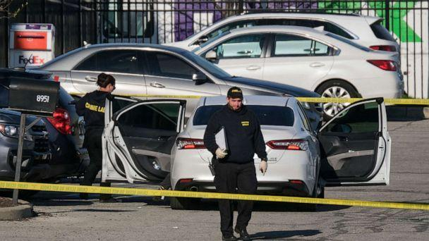 PHOTO: Crime scene investigators walk through the parking lot at a FedEx facility in Indianapolis, April 16, 2021. (Jeff Dean/AFP via Getty Images)