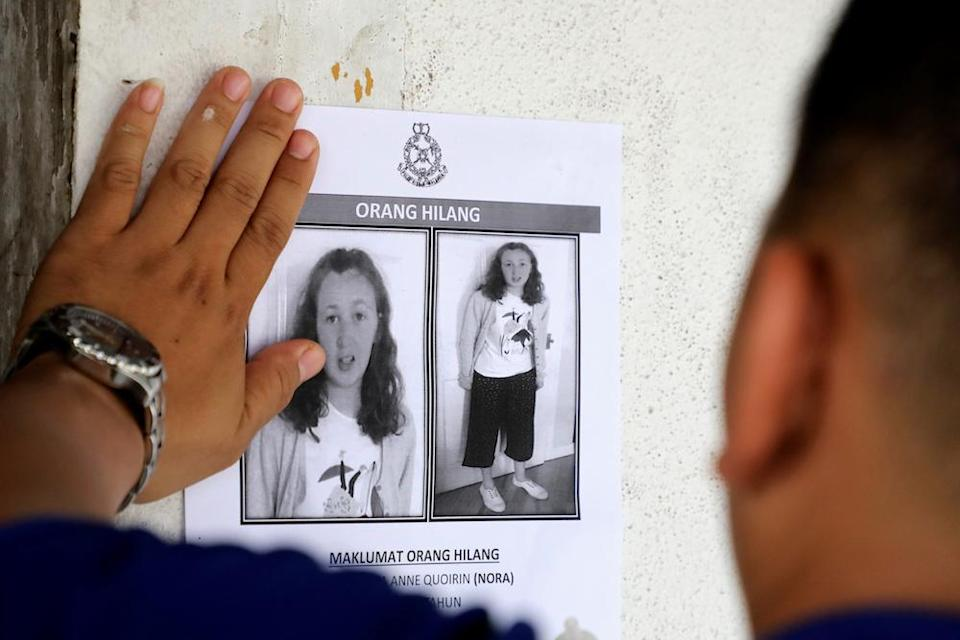 A police officer pastes a photo of 15-year-old Irish girl Nora Anne Quoirin who went missing from a resort on a wall at a shop in Seremban August 9, 2019. — Reuters pic
