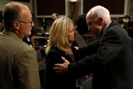 U.S. Senator John McCain (R) consoles Theresa and Sid Palmer, whose son U.S. Navy sailor Logan Palmer was killed in a collision aboard the USS McCain in August, after a Senate Armed Services Committee hearing on recent fatal United States Navy ship collisions at sea, on Capitol Hill in Washington, U.S. September 19, 2017. REUTERS/Jonathan Ernst