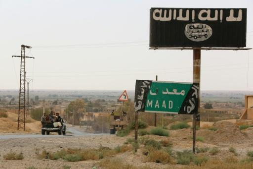 A vehicle drives past a billboard bearing the logo of the Islamic State group in Syria's Deir Ezzor province on September 24, 2017