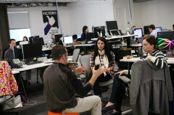 Employees gather in their work environment for a discussion at the new headquarters of Facebook in Menlo Park, California January 11, 2012.