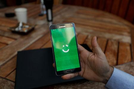 FILE PHOTO: Employee shows the logo of Careem on his mobile in his office in the West Bank city of Ramallah
