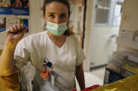 Medical staff member Alexandra Pichon Dignac pauses as Lolita Andela and Caroline Erganian, arrive on the eve of their surgery, at Bichat Hospital, AP-HP, in Paris, Tuesday, Dec. 1, 2020. Hospitals are increasingly grappling with giant backlogs of surgeries that were postponed when COVID-19 hit. One of the biggest hospitals in Paris, Bichat Hospital, this month reopened all 22 of its operating rooms. It is once again performing surgeries that were stopped during virus surges that pushed France's death toll past 55,000. (AP Photo/Francois Mori)